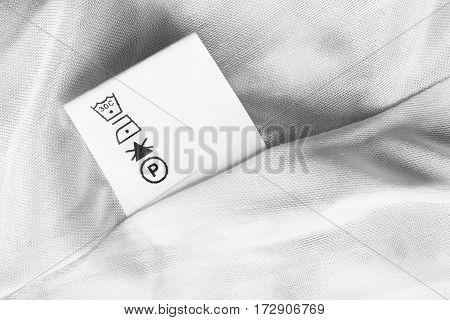 Washing instructions label on white satin closeup