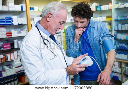 Pharmacist checking blood pressure of customer in pharmacy
