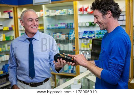 Customer entering pin in payment terminal machine while purchasing medicines in pharmacy
