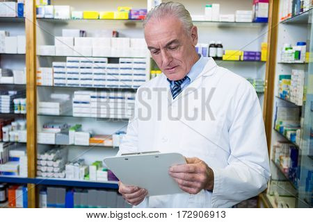 Pharmacist reading a prescription in pharmacy