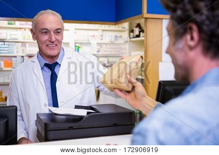 Pharmacist giving medicine package to customer at counter in pharmacy