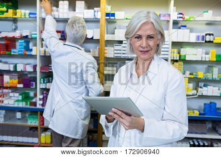 Pharmacist using digital tablet and co-worker checking medicines in background at pharmacy