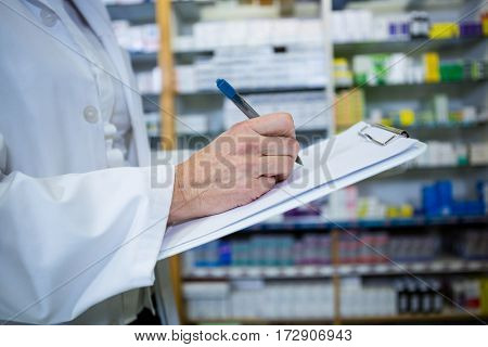 Pharmacist writing on clipboard in pharmacy