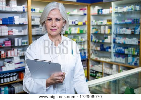 Portrait of pharmacist holding a clipboard in pharmacy
