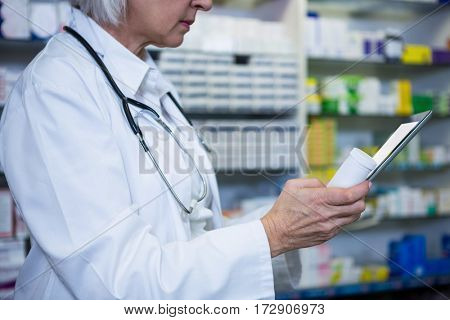 Pharmacist holding digital tablet while checking medicine in pharmacy