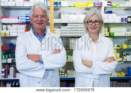 Portrait of pharmacists standing with arms crossed in pharmacy