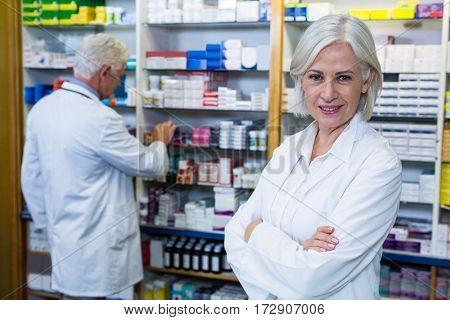 Pharmacist standing with arms crossed and co-worker checking medicines in background at pharmacy
