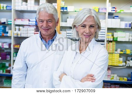 Portrait of smiling pharmacists standing in pharmacy