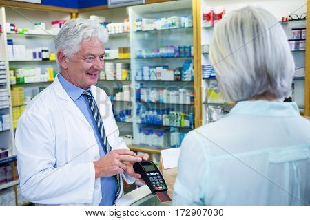 Customer making payment through payment terminal machine at pharmacy