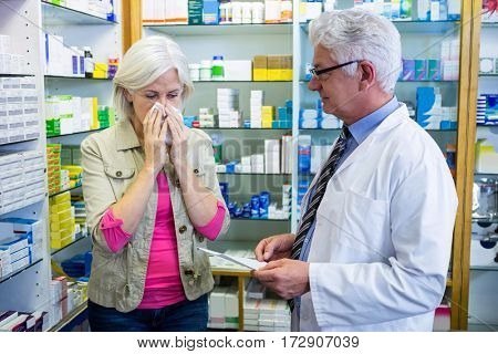 Customer sneezing while giving prescription to pharmacist in pharmacy