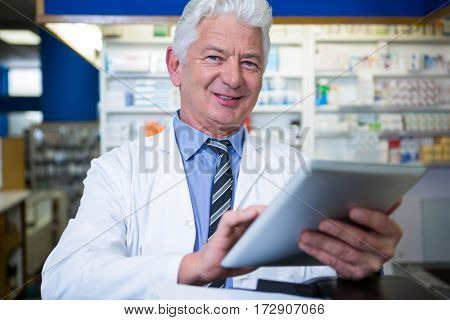 Portrait of pharmacist using a digital tablet in pharmacy