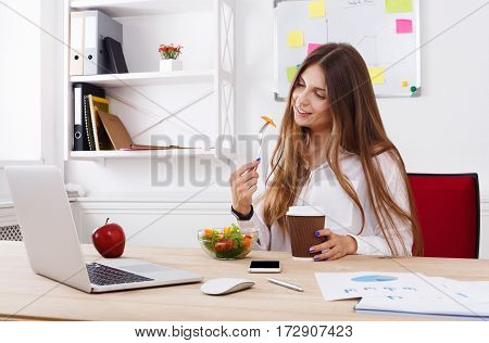 Woman eating healthy business lunch in modern office interior. Young beautiful businesswoman at working place has vegetable salad in bowl, diet and vegetarian nutrition concept.