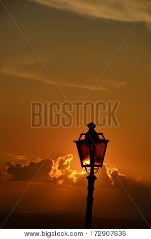 A Lit Vertical Lightposts with Sunrise Background