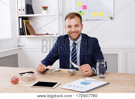 Man eating healthy business lunch of vegetable salad in modern office. Young handsome businessman at working place, looking at camera, diet and eating right concept.