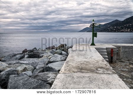 Winter evening view of the breakwater dam of Camogli, along the shores of Ligurian Sea (Northern Italy). Color image.