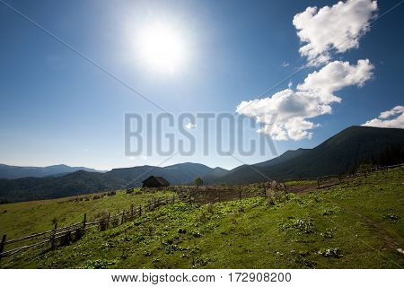 Meadow enclosed by wooden fence on background of beautiful mountain landscape sun and clouds. In distance is old wooden house. To hut is barely noticeable path.