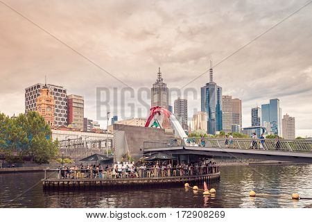 Melbourne Australia - December 27 2016: Ponyfish Island Cafe and south bank pedestrian bridge with people in the evening