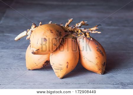 Bunch of ripe scratched orange mangoes on wooden floor. Close-up