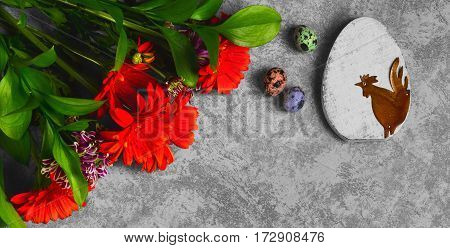 Easter card. On gray concrete background wooden eggs with Easter rooster quail eggs. Easter bouquet of chrysanthemum. Top view from above and copy space.