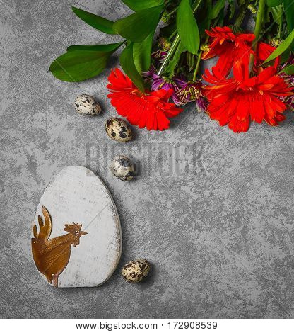 Easter card. On gray concrete background wooden eggs with the Easter rooster quail eggs. Easter bouquet of chrysanthemum. Top view from above and copy space.