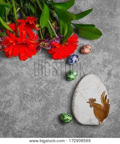Easter card. On gray concrete background Two wooden eggs with the Easter rooster quail eggs. Easter bouquet of chrysanthemum. Top view from above and copy space.