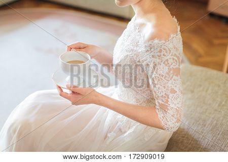 the elegant bride in a white wedding lacy dress holds a tea cup in hand. relaxation before a wedding ceremony. morning tea drinking.