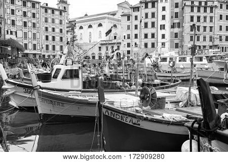 CAMOGLI GENOA, ITALY - FEBRUARY 12, 2017: the world famous fishing harbour of the village of Camogli, along the shores of Ligurian Region (Northern Italy), during the wintertime. Some fishing boats are moored for the winter season. Black and white photo.