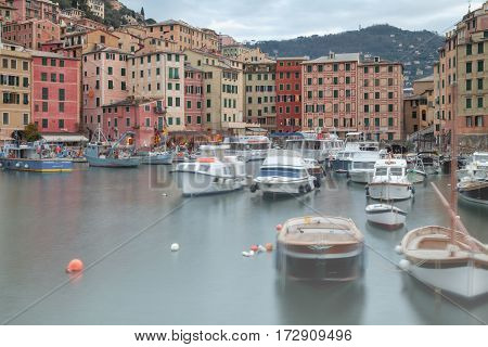 The world famous fishing harbour of the village of Camogli, along the shores of Liguria region (Northern Italy), during the wintertime; in the background the typical pastel-coloured houses.