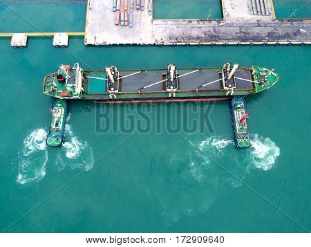 ship berthing at port with tug assistance on mooring rope