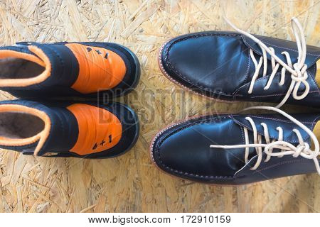 Big and small shoes on wooden background concept of family
