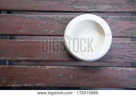 White ceramic ashtray on a wooden background