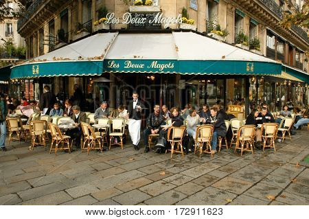 People Eating And Drinking In A Street Restaurant Of Paris