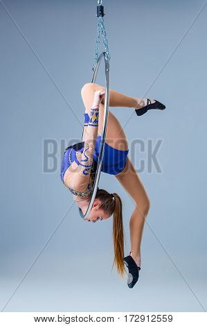 Cute artistic gymnast exercising with hanging hoop on a blue background