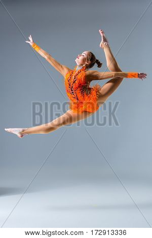 Young slim gymnast in studio. jump. Gymnast on a blue background