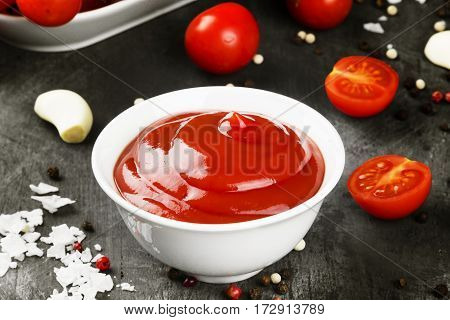 Tomato Sauce In White Bowl, Spice And Cherry Tomatoes On A Dark Background. Toning.