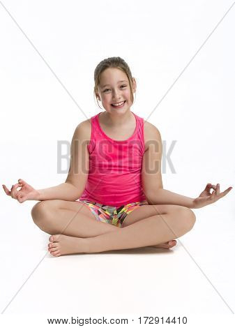Young Tween girl sitting in a yoga pose on a white background