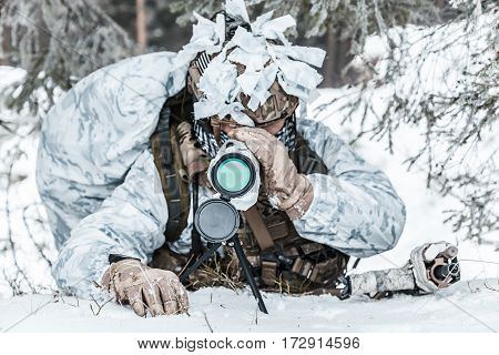 Winter arctic mountains warfare. Action in cold conditions. spotter seeking for enemy in wait somewhere above the Arctic circle