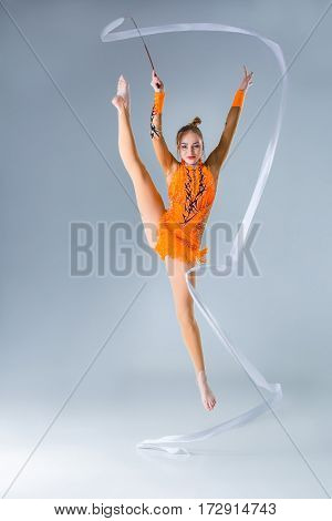 beautiful Caucasian girl gymnast with white ribbon on a blue background