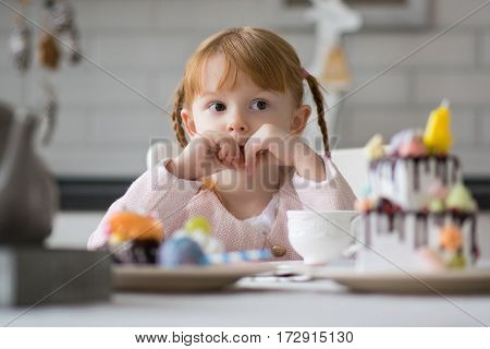 Very nice charming little girl in pink jaket in bright interior of the house