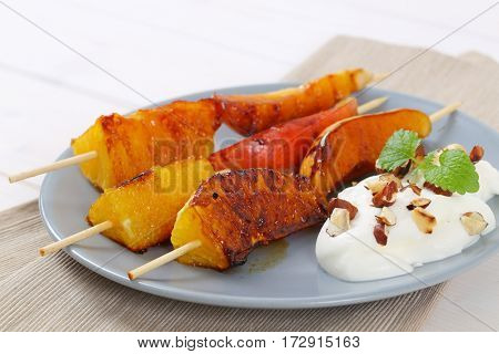 plate of pear and orange skewers with yogurt, chopped nuts and almonds - close up
