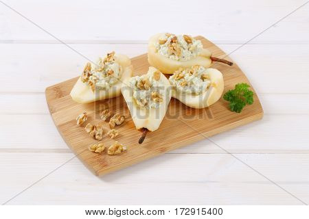 halved pears with blue cheese and walnuts on wooden cutting board