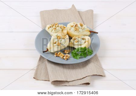 plate of halved pears with blue cheese and walnuts on beige place mat