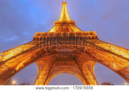 PARIS - MARCH 14: Eiffel Tower brightly illuminated at dusk on Mar 14 2015 in Paris. The Eiffel tower is the most visited monument of France.