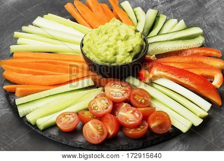 Traditional Latin American sauce guacamole in a bowl and various vegetables (carrots tomatoes cucumbers celery) on a dark background
