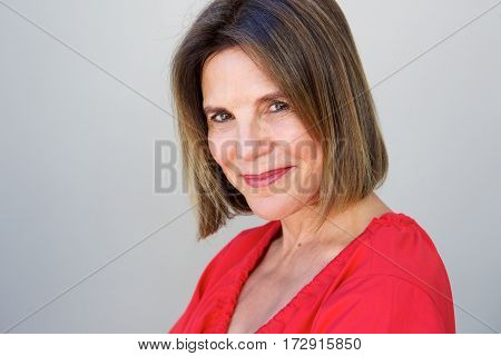 Portrait of attractive older woman smiling against gray background poster