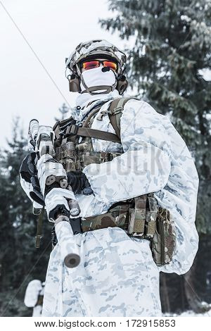 Winter arctic mountains warfare. Action in cold conditions. Trooper with weapons in forest somewhere above the Arctic Circle. Low angle view
