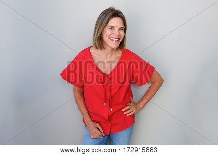 Attractive Older Woman Laughing Against Gray Wall