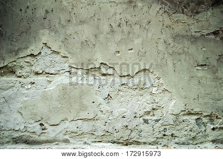 Old chipped plaster on the concrete wall