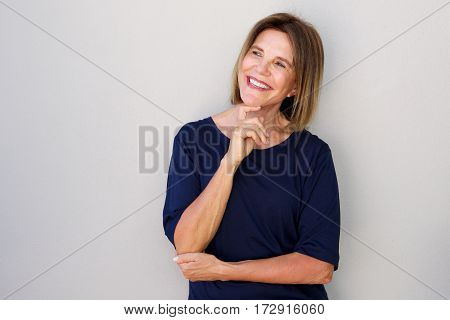 Portrait of happy older woman with hand to chin poster