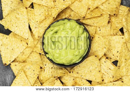 Traditional Latin American Sauce Guacamole In A Bowl And Nachos On A Dark Background. Top View, Copy